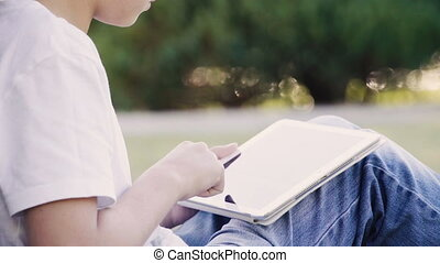 Young teenage boy sitting on the grass and using digital tablet