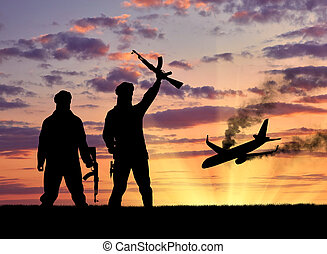 Concept of terrorism and acts of terrorism. Silhouette of terrorists and blow up the plane wreck at sunset