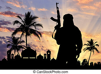 Concept of terrorism. Silhouette of a terrorist with weapons near the town hall at sunset