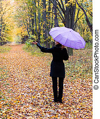 Lonely woman with bright umbrella in autumn forest