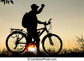 Concept of the winner. Silhouette of a cyclist at sunset with a raised hand