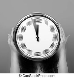 Concept of time passing - Woman holding blured clock