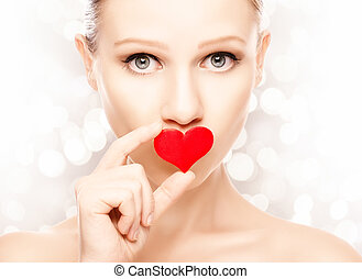 concept of Valentine's Day. girl with a red heart on lips
