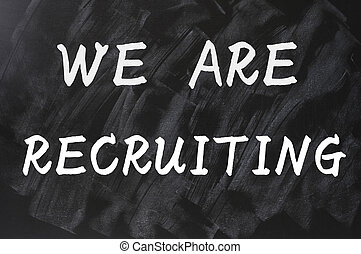 Concept of we are recruiting written on smudged blackboard ...
