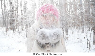 Concept of winter entertainment. Young woman having fun blowing fresh snow from her hands