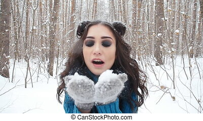 Concept of winter entertainment. Young woman in winter park with snow in hands