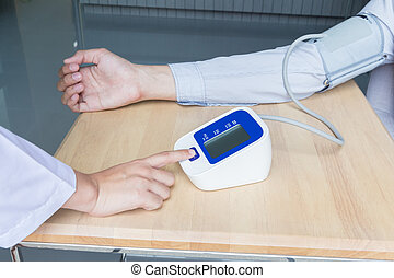 Woman doctor press start button on blood pressure