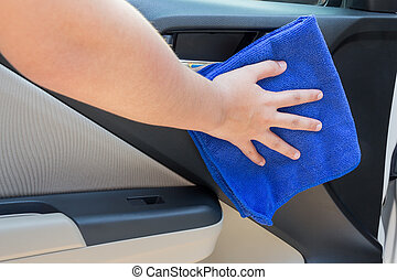 Concept of Woman hand cleaning interior car door panel with microfiber cloth.