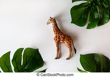 Concept of World giraffe protection day. Little toy realistic giraffe cub in center of frame, green monstera leaves around edges. White background, close-up, top view. Horizontal