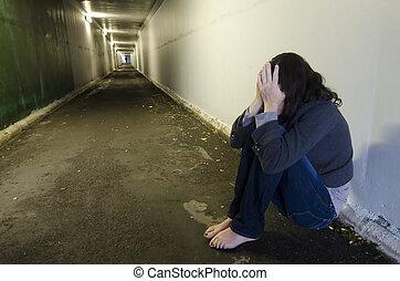 Crime scene concept photo of rape victim. A sad woman sits on the floor of a dark tunnel.