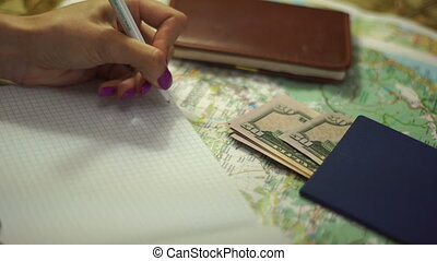 Concept planning vacations - girl makes notes in a Notepad....