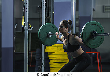 Powerful attractive muscular woman Cross Fit trainer do workout with barbell
