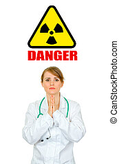 Concept- radiation danger! Frustrated medical doctor woman praying
