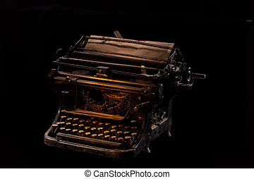 Concept shot of antique manual typewriter with paper on black background, selective focus