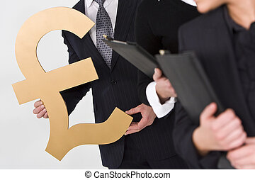 Concept shot showing business people standing in a line, the last of whom is carrying a large golden British Pound Sterling symbol