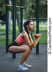 Young strong girl do exercises during street workout