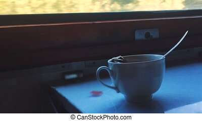 concept travel train wagon. cup of tea is on the table by...