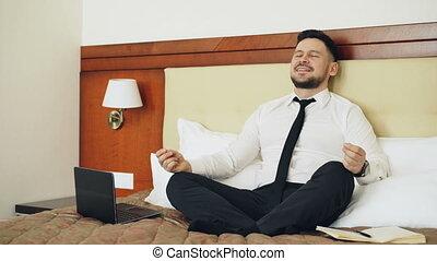 concept, yoga, lit, professionnels, lotus, ordinateur portable, séance, fermé, hôtel, voyage, room., informatique, prendre, position, mettre, homme affaires, sourire, décontracté