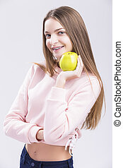 Concepts of Dental Health. Portrait of Satisfied Smiling Caucasian Teenage Girl with Teeth Braces. Posing with Green Apple.