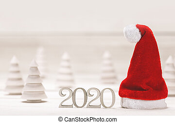 Conceptual 2020 new year background with small wooden fir trees 2020 number and red santa claus hat
