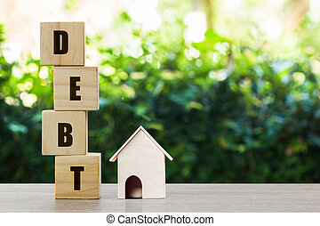 Conceptual about property debt. A small house model with stack of wooden block on nature background. Depicts debt resulting from the purchase of an expensive house