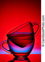 Conceptual composition of two glass teacups over colored red background, close-up, vertical.