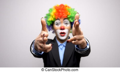 Conceptual footage of clown in business suit shooting from...