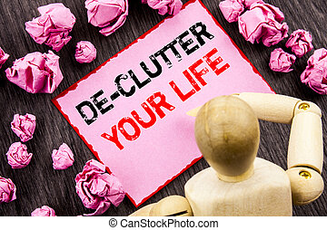 Conceptual hand text showing De-Clutter Your Life. Concept meaning Free Less Chaos Fresh Clean Routine written on Sticky Note Holding By Sculpture on the wooden background.