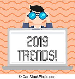Conceptual hand writing showing 2019 Trends. Business photo showcasing general direction in which something is developing or changing Man Holding and Looking into Binocular Behind Laptop Screen.