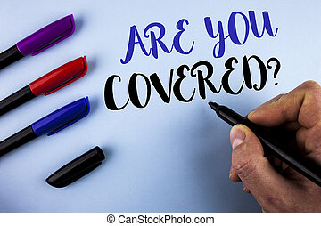 Conceptual hand writing showing Are You Covered Question. Business photo text Health insurance coverage disaster recovery written by Man on plain background Markers next to it.