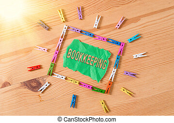 Conceptual hand writing showing Bookkeeping. Business photo showcasing keeping records of the financial affairs of a business Colored crumpled papers wooden floor background clothespin.