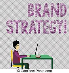 Conceptual hand writing showing Brand Strategy. Business photo showcasing long term plan development of successful brand achieve goals Businessman Sitting on Chair Working on Computer and Books.
