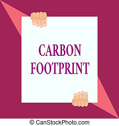 Conceptual hand writing showing Carbon Footprint. Business photo showcasing amount of dioxide released atmosphere result of activities Two hands hold one big white paper placed on top and bottom.