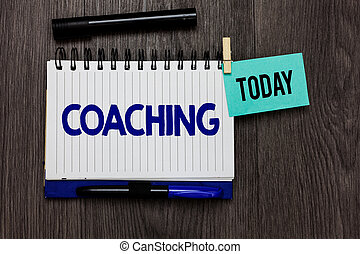 Conceptual hand writing showing Coaching. Business photo text person supports client in achieving specific personal goal Ideas notebook wooden table markers for today important reminder.