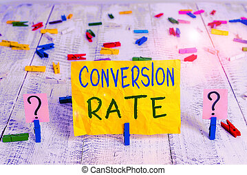 Conceptual hand writing showing Conversion Rate. Concept meaning number of visitors to a website that complete a desired goal Crumbling sheet with paper clips placed on the wooden table