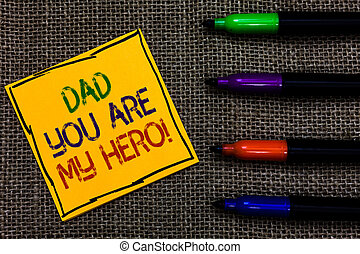 Conceptual hand writing showing Dad You Are My Hero. Business photo text Admiration for your father love feelings compliment Written on black lined yellow transverse note pen jute ground.