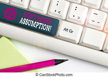 Conceptual hand writing showing Don T Make Assumption. Business photo showcasing something that you assume to be case even without proof White pc keyboard with note paper above the white background.