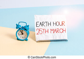 Conceptual hand writing showing Earth Hour 25Th March. Business photo text symbol commitment to planet Organized World Wide Fund Alarm clock beside a Paper sheet placed on pastel backdrop.