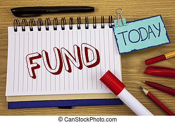 Conceptual hand writing showing Fund. Business photo text Large amount of money is released from bank for particular purpose written on Noteoad on wooden background Today Pen Pencil next to it