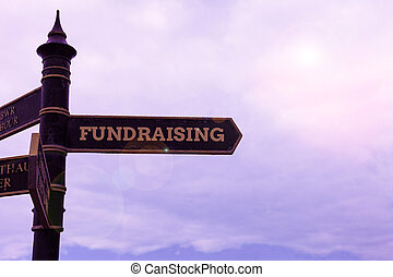 Conceptual hand writing showing Fundraising. Business photo text act of collecting or producing money for a particular purpose Road sign on the crossroads with blue cloudy sky in the background.