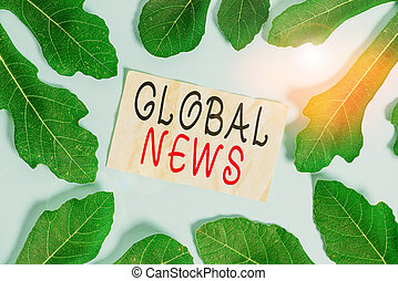 Conceptual hand writing showing Global News. Business photo showcasing world noteworthy information about recent or important events Leaves surrounding notepaper above empty soft pastel table.