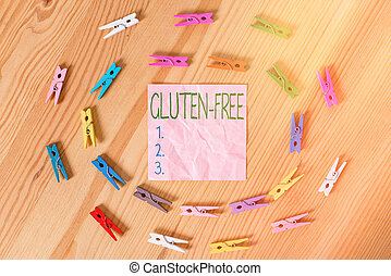 Conceptual hand writing showing Gluten Free. Concept meaning excludes the tenacious elastic protein substance of wheat flour Colored crumpled papers wooden floor background clothespin