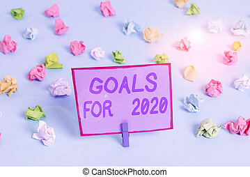 Conceptual hand writing showing Goals For 2020. Business photo text The following things you want to have and achieve in 2020 Colored crumpled papers empty reminder blue floor clothespin.