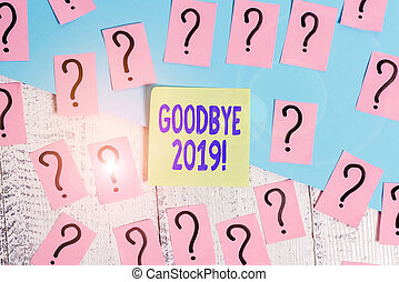 Conceptual hand writing showing Goodbye 2019. Business photo text express good wishes when parting or at the end of last year Crumbling papers with thick cardboard on the wooden table.