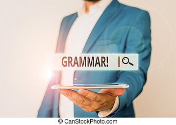 Conceptual hand writing showing Grammar. Concept meaning whole system structure language syntax and morphology Man in blue suite and white shirt holds mobile phone in hand