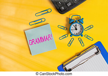 Conceptual hand writing showing Grammar. Concept meaning whole system structure language syntax and morphology Alarm clock clipboard clips calculator notepad colored background