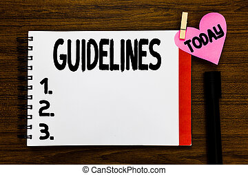Conceptual hand writing showing Guidelines. Business photo text General rule principle piece of advice Policies Instructions Open notebook page markers holding paper heart wooden background.
