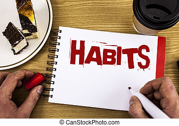 Conceptual hand writing showing Habits. Business photo showcasing Regular tendency or practice Routine Usual Manners Behavior Pattern written by Man on Notebook on wooden background Cake and Cup.