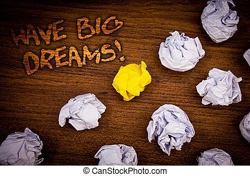 Conceptual hand writing showing Have Big Dreams Motivational Call. Business photo showcasing Future Ambition Desire Motivation Goal Words wooden desk crumbled white yellow paper.