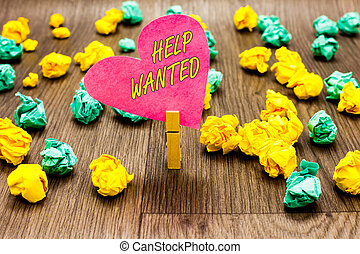 Conceptual hand writing showing Help Wanted. Business photo text advertisement placed in newspaper by employers seek employees Clothespin holding pink paper heart crumpled papers several tries.
